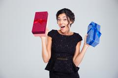 Woman in black dress holding two gift boxes - stock photo