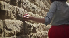 Girl is Walking along Wall and Touching it with Hand - stock footage