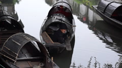 Boatman resting in Black-awning boats on canal Stock Footage