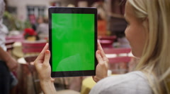 Girl is Holding Tablet PC in Portrait Mode in Outdoor Coffee Shop - stock footage