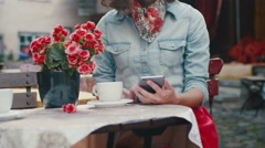 Young Girl is Using Mobile Phone in Outdoor Coffee Shop Stock Footage
