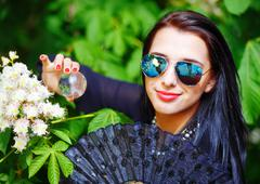 Beautiful Girl with flowers, and sunglasses, posing next to blooming magical Stock Photos