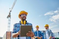Builder in hardhat with tablet pc at construction Stock Photos
