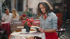 Smiling Girl is Using Tablet in Outdoor Coffee Shop Stock Footage