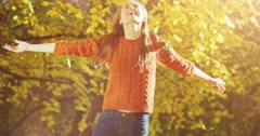 Happy woman throwing leaves in Autumn, sunny park, smiling. Slow Motion 120 fps. - stock footage