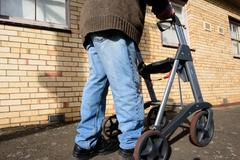 Elderly man with walking frame on sunny day - stock photo