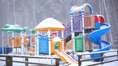Park playground covered in snow. Children with mother playing on the playground Stock Footage