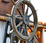 Close up of a steering wheel of the ship - stock photo