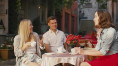 Happy Young People are Talking in Outdoor Coffee Shop - stock footage