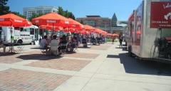4K food trucks gathering with people sitting at outdoor tables with blue sky Stock Footage