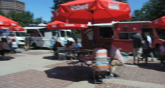 4K pan of community food trucks gathering with Denver skyline blue sky Stock Footage
