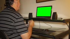 MAN SNAPPING FINGERS LISTENING TO MUSIC on laptop computer green screen Stock Footage