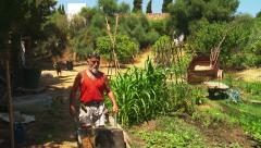 Organic gardener with wheelbarrow Stock Footage