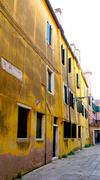Stock Photo of Alley with ancient yellow decay wall building