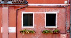 two windows and drained pipe with coral color wall - stock photo