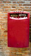 red postal box public on brick wall - stock photo
