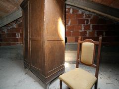 wooden wardrobe and an antique chair in the dusty attic - stock photo