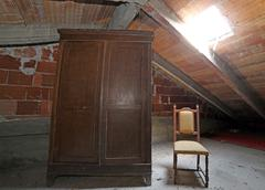 Wooden wardrobe and an antique chair in the dusty attic Stock Photos