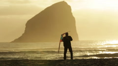 MAN SETS OFF KITE ON BEACH AT SUNSET WITH ROCK FORMATION IN BACKGROUND Stock Footage