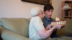 Grandma, elderly woman, young man, family, blowing birthday candles, cake Stock Footage