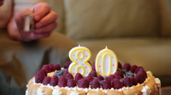 Elderly woman, alone, grandmother, 80 years old,lighting candles, birthday cake Stock Footage
