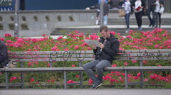 Man sitting on a bench and reading in Berlin Stock Footage