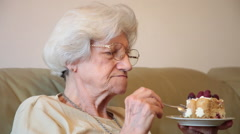 Elderly woman eating tasty birthday cake at home, 80 years old grandmother Stock Footage