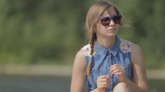 Girl in dress and sunglasses unbutton sitting on the beach Stock Footage