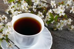 White cup of tea with flowers of a cherry - stock photo