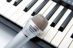 The microphone lies on the synthesizer keyboard Stock Photos