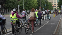 People bicycle home from work on cycle path, city centre, Dublin, Ireland Stock Footage
