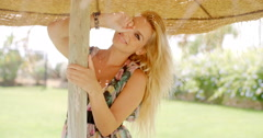 Pretty Woman Under Thatched Hut Smiles at Camera Stock Footage