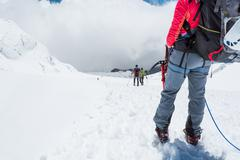 Alpinist looking down the slope. Stock Photos