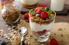 Yogurt with baked granola and berries in small glass - stock photo