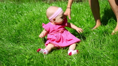 Seven month baby play on grass and her mother is ready to catch her from falling Stock Footage