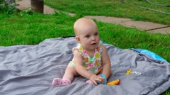 A little baby plays, baby plays on a carpet with cucumber a plastic toy Stock Footage