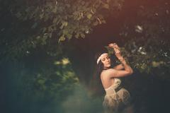 Romantic, beautiful pregnant woman outside in the park among trees  and greenery Stock Photos