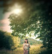 Romantic pregnant woman outside, among the trees and greenery like in fairytale Stock Photos
