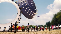 Many Children have fun Near Big Bol Spinning Round shape Kites Stock Footage