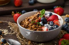 Yogurt with baked granola and berries in small bowl - stock photo