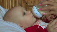 Seven month old baby holds a bottle with milk Stock Footage