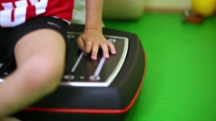 Little boy sits on working vibrating platform in medical center. Stock Footage