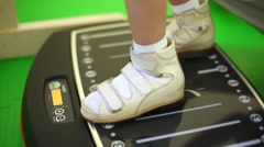 Legs of little boy standing on working vibrating platform. Stock Footage