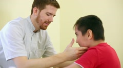 Doctor supports child during physiotherapy treatment. Stock Footage