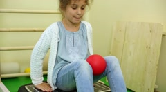 Little girl sits on vibration platform, squeezing ball by knees Stock Footage