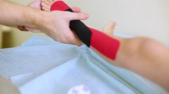 Hands of physician put fixing tape on the child feet. Stock Footage