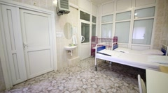 Hospital ward with several beds, table and washing basin. Stock Footage