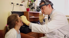 Ophthalmologist examines  girl eyes through ophthalmoscope. - stock footage