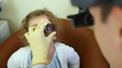 Ophthalmologist inspects girl eye through lens Stock Footage