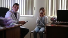 Girl checks sight at reception of ophthalmologist in shady room. Stock Footage